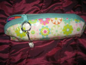 Flower power! It's tiny but holds a lot...that's why I love it. The key ring on the zipper is a porcelain clog from Holland.